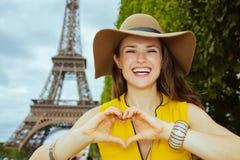 A mulher na moda de sorriso que mostra o coração deu forma às mãos fotografia de stock
