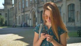 Mulher na moda encantador do gengibre nos óculos de sol que datilografa no telefone e na posição na rua com construção no fundo video estoque