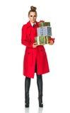 Mulher na moda no revestimento vermelho no branco com as caixas do presente de Natal Imagem de Stock