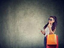 Mulher na moda pensativa com sacos de compras e telefone fotos de stock royalty free