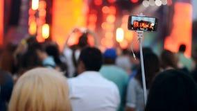 Mulher na multidão que faz o vídeo em seu smartphone no concerto ao ar livre da música filme