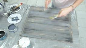 A mulher na oficina está trabalhando nas placas de madeira, criando um efeito da antiguidade vídeos de arquivo