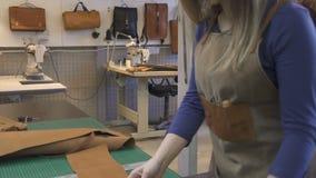 Mulher na parte de medição do juntamento de couro marrom artificial pela régua na oficina vídeos de arquivo
