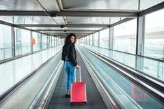 Mulher na passagem movente no aeroporto com uma mala de viagem cor-de-rosa foto de stock