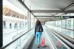 Mulher na passagem movente no aeroporto com uma mala de viagem cor-de-rosa imagem de stock royalty free