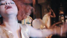 Mulher na peruca vermelha luxúria do cabelo que faz caretas para a câmera e que dança na cena com trupe vídeos de arquivo