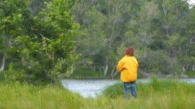 Mulher na pesca do revestimento amarelo que gerencie no lago video estoque