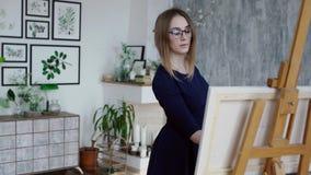 Mulher na pintura do vestido em um estúdio vídeos de arquivo