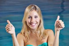 Mulher na piscina que mantém os polegares Foto de Stock