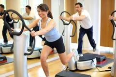 Mulher na placa da vibração em um gym fotos de stock