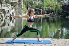 Mulher na pose do guerreiro fora, ioga Fotos de Stock