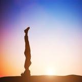 Mulher na pose principal da ioga do suporte que medita no por do sol zen Fotografia de Stock