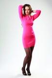 Mulher na posição cor-de-rosa do vestido imagem de stock