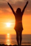 A mulher na praia alcança acima no por do sol imagens de stock royalty free