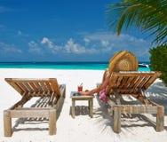 Mulher na praia com chaise-salas de estar imagens de stock