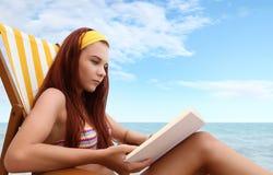 Mulher na praia com um livro fotos de stock