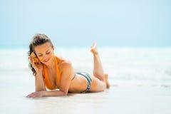 Mulher na praia e no som de escuta do mar no shell Imagem de Stock