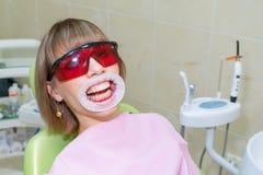 A mulher na recepção no dentista, em clarear dos dentes e na prevenção imagens de stock royalty free