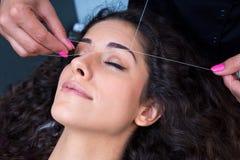 Mulher na remoção dos pêlos faciais que rosqueia o procedimento fotografia de stock royalty free