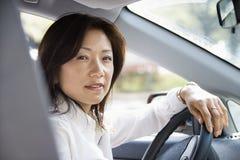 Mulher na roda de direcção fotografia de stock