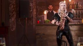 A mulher na roupa de couro preta 'sexy' executa uma música em um saxofone vídeos de arquivo