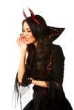 Mulher na roupa do diabo que sussurra a alguém fotografia de stock royalty free