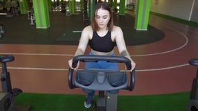 A mulher na roupa do esporte está dando certo na bicicleta de exercício no gym verde Foto do close-up, acima da vista video estoque