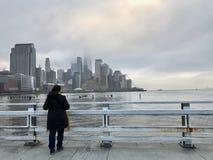 A mulher na roupa escura olha a ilha de Manhattan da liberdade de Hudson River Embankment imagem de stock royalty free