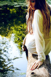 Mulher na roupa molhada e no cabelo molhado que sentam-se em um ramo de árvore próximo imagem de stock