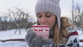 Mulher na roupa morna que bebe o chá ou o café quente do copo na manhã 4k do inverno vídeos de arquivo