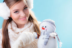Mulher na roupa morna que guarda o brinquedo do boneco de neve Fotografia de Stock