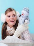 Mulher na roupa morna que guarda o brinquedo do boneco de neve Fotos de Stock