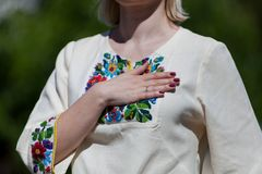 Mulher na roupa nacional de Ucrânia embroidery Guarda sua mão em sua caixa e canta um hino imagens de stock royalty free