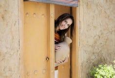 Mulher na roupa tradicional que olha entrada direta e velha dentro Fotos de Stock Royalty Free
