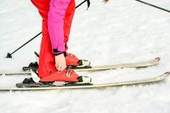 Mulher na roupa vermelho-cor-de-rosa que veste calçados do esqui para esquiar foto de stock royalty free