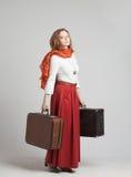 Mulher na saia vermelha do vintage com malas de viagem Imagem de Stock Royalty Free