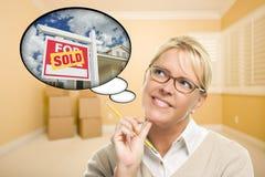 Mulher na sala vazia com bolha do pensamento do sinal vendido de Real Estate fotografia de stock