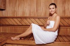 A mulher na sauna mostra o polegar acima Fotografia de Stock Royalty Free