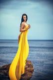 Mulher na tela amarela na rocha Fotografia de Stock Royalty Free