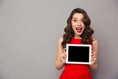 Mulher na tela de tablet pc vermelha da placa do showig do vestido imagem de stock