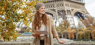 Mulher na terraplenagem em Paris que guarda o mapa e que olha de lado Foto de Stock