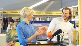 Mulher na verificação geral do supermercado, está pagando usando um cartão de crédito vídeos de arquivo