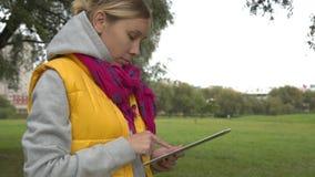 Mulher na veste amarela usando o PC da tabuleta no parque video estoque