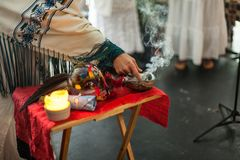 A mulher na veste cerimonial está tocando no sábio de fumo imagens de stock
