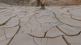 A mulher nas botas de couro anda no solo seco do esboço filme