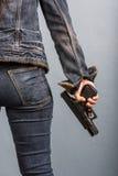 A mulher nas calças de brim está guardando uma arma Fotos de Stock Royalty Free