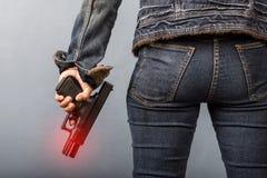 A mulher nas calças de brim está guardando uma arma Imagem de Stock Royalty Free