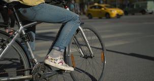 Mulher nas calças de brim que esperam em sua bicicleta em uma interseção ocupada e que montam então Movimento lento disparado em  video estoque