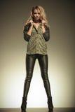 Mulher nas calças de couro que levantam guardando seu colar fotografia de stock royalty free
