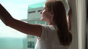 Mulher nas cortinas brancas da revelacão do t-shirt e a vista fora da janela Apreciando o mar veja 100 fps filme